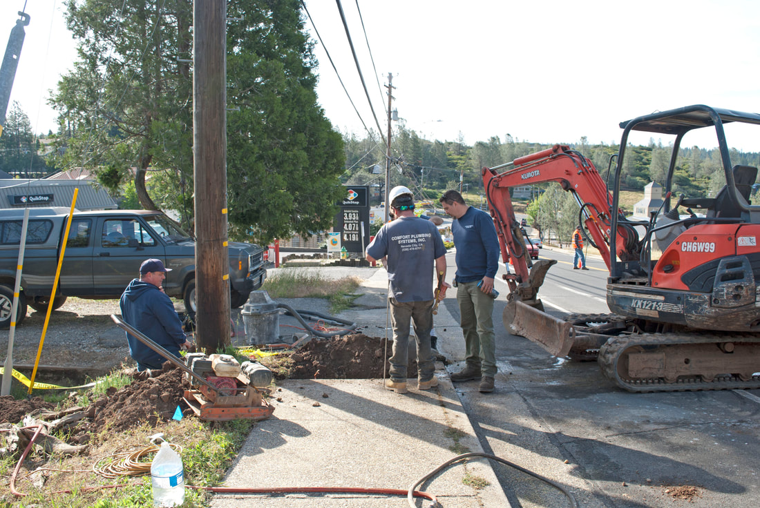 Hooking up  a new home to city sewer system, digging sewer lines on sidewalk and street using tractors and shutting down street Nevada City, CA